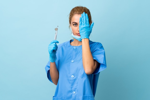 Young woman dentist holding tools over isolated blue covering a eye by hand