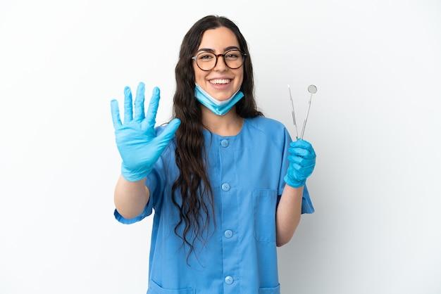 指で5を数える白い背景で隔離のツールを保持している若い女性