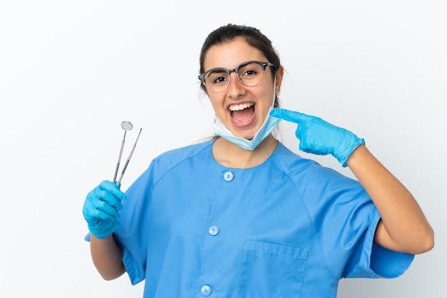 親指を立てるジェスチャーを与える白い背景で隔離のツールを保持している若い女性の歯科医