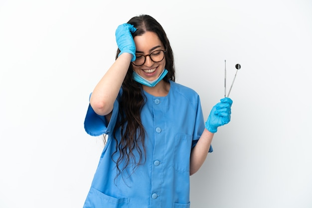 Молодая женщина-стоматолог, держащая инструменты, изолированные на белом фоне, смеясь