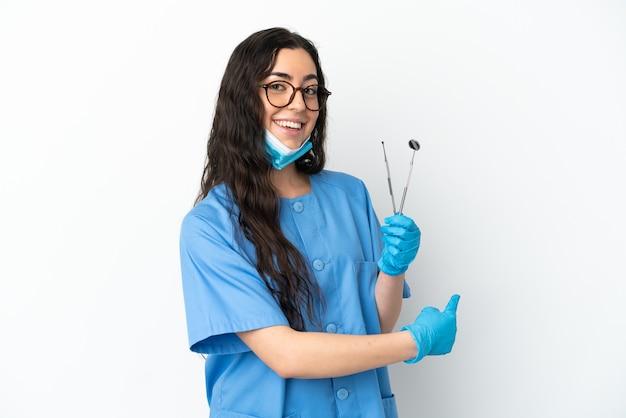 後ろ向きの白い背景で隔離のツールを保持している若い女性の歯科医