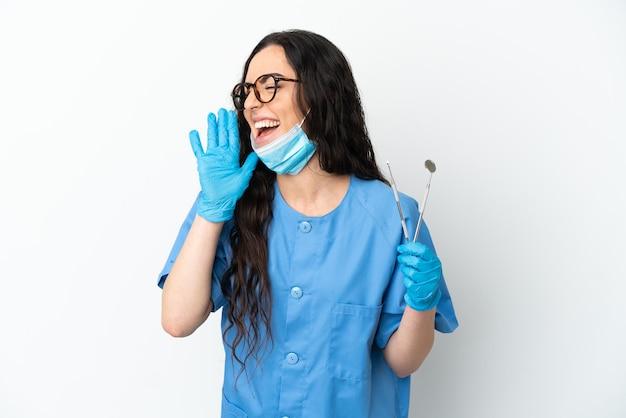 Молодая женщина-дантист, держащая инструменты, изолированные на белом фоне, кричит с широко открытым ртом в сторону