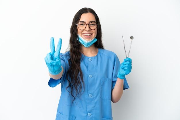 Молодая женщина-стоматолог, держащая инструменты, изолированные на белом фоне, улыбается и показывает знак победы