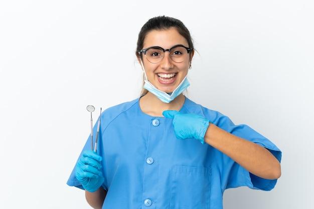 驚きの表情で白い背景で隔離のツールを保持している若い女性の歯科医