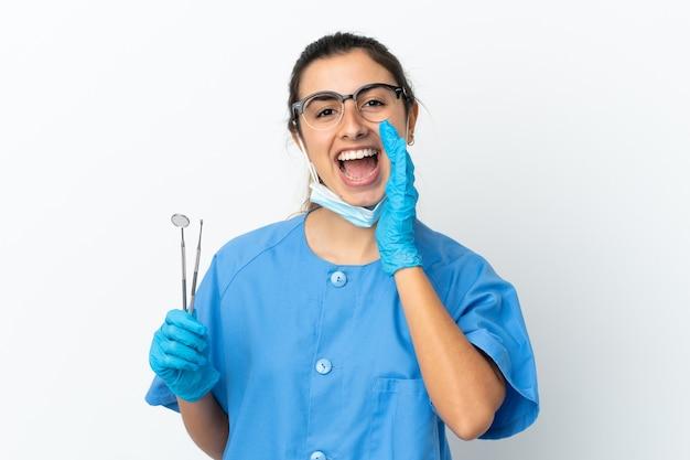 Молодая женщина-дантист, держащая инструменты, кричит с широко открытым ртом