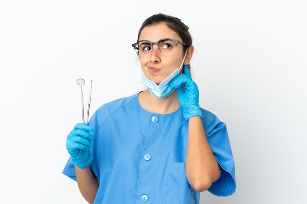 Young woman dentist holding tools isolated on white background having doubts
