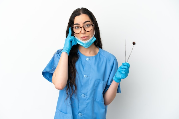 Young woman dentist holding tools isolated on white background thinking an idea