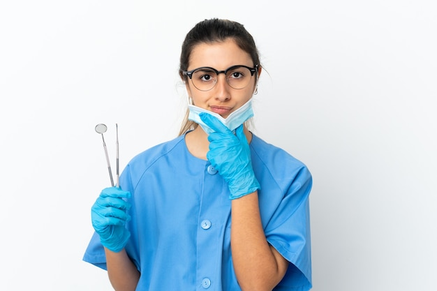 Young woman dentist holding tools isolated on white background thinking