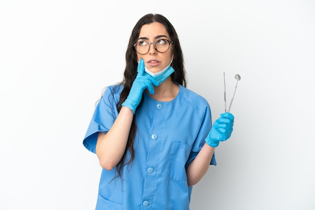 Young woman dentist holding tools isolated on white wall having doubts while looking up
