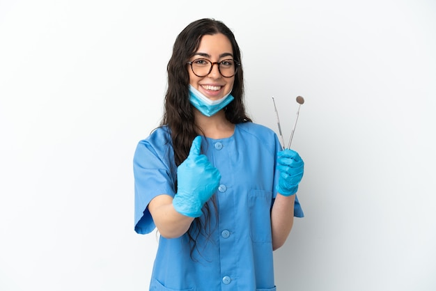 Young woman dentist holding tools isolated