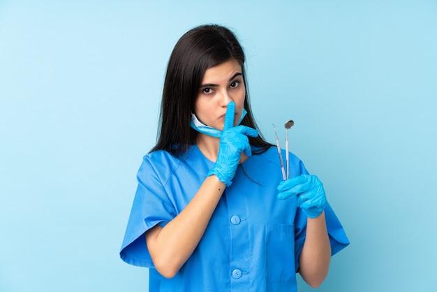沈黙のジェスチャーをしている孤立した青い壁の上にツールを保持している若い女性の歯科医
