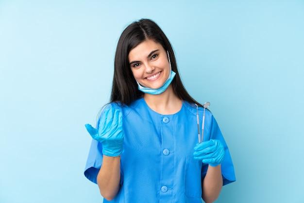来て招待して分離の青い壁にツールを保持している若い女性歯科医