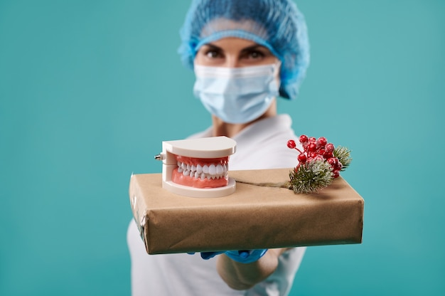 Молодая женщина-дантист в шляпе и маске держит рождественский подарок на ладони.