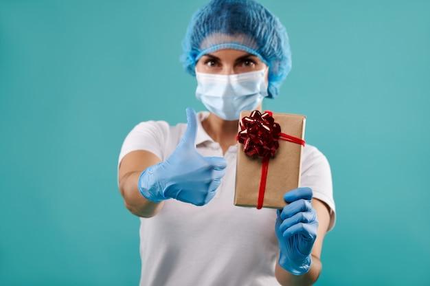 Молодая женщина-дантист в шляпе и маске держит рождественский подарок.
