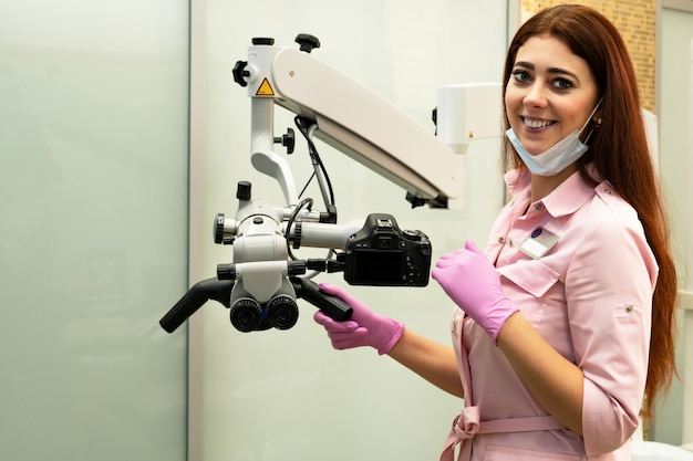 Young woman dentist and professional microscope in a dental clinic
