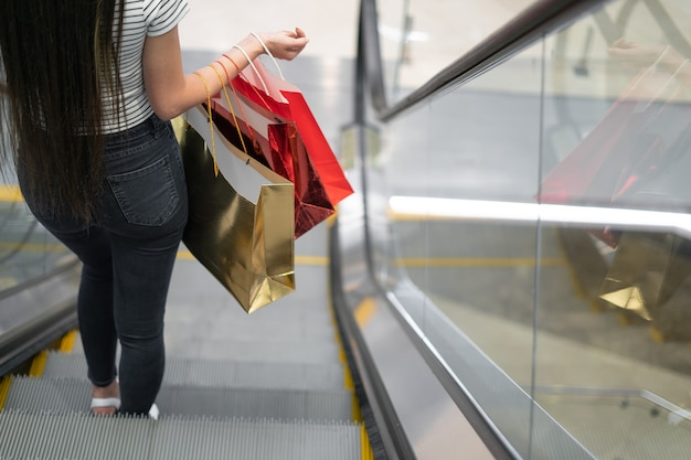 A young woman descends on an escalator in a shopping center. hold paper bags in your hands. black friday. shopping before the holiday