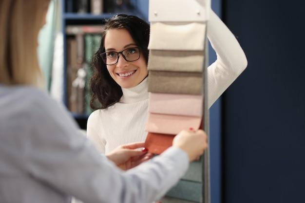 젊은 여성 디자이너가 판매원과 이야기하고 직물에서 커튼용 직물을 선택하고 있습니다