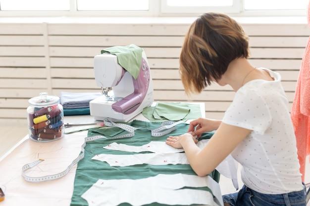 Молодая женщина-дизайнер делает отметки для нового шитья, сидя за столом рядом с шитьем