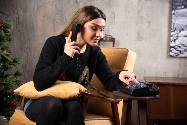크리스마스 트리 옆에 전화 걸기 젊은 여자.