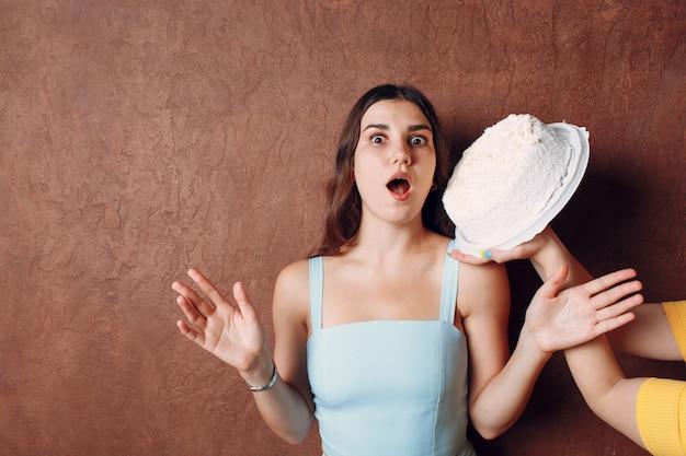 Молодая женщина окунает лицо в белый торт со сливками на фоне коричневой стены. концепция с днем рождения.