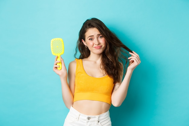 Young woman disappointed with hair loss condition, showing hair brush, standing upset against blue background.