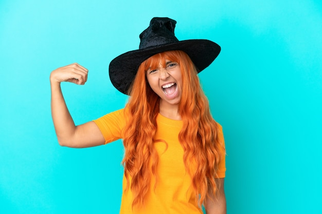 Young woman disguised as witch isolated on blue background doing strong gesture