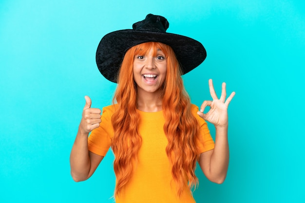 Young woman disguised as witch isolated on blue background showing ok sign and thumb up gesture