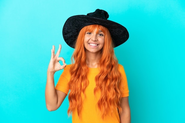 Young woman disguised as witch isolated on blue background showing ok sign with fingers