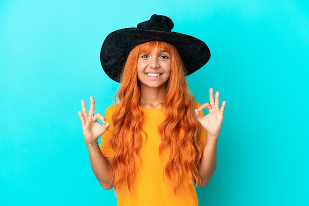Young woman disguised as witch isolated on blue background showing an ok sign with fingers