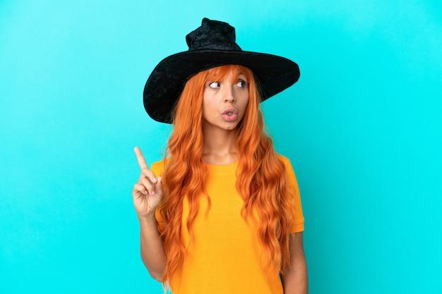 指を上に向けるアイデアを考えて青い背景に分離された魔女を装った若い女性