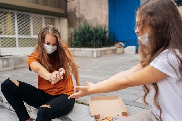 Молодая женщина дезинфицирует руки подруги перед едой пиццы