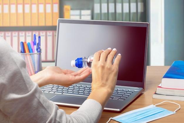 ノートパソコンでオフィスの机の上で彼女の手を消毒する若い女性。コンピュータのキーボードを使用するときの衛生と健康管理。