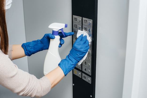 A young woman disinfects and cleans keys in an elevator during a global pandemic. stay at home.