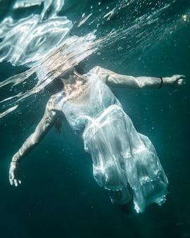 Молодая женщина, ныряющая в белом платье