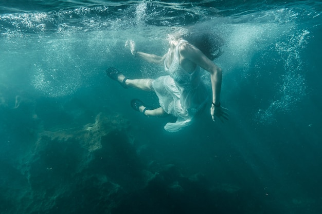 Young woman diving with a white dress
