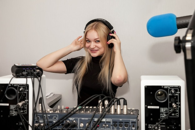 ヘッドフォン、マイク、サウンドミックスコンソール、トークニュースライブを備えたスタジオの若い女性djラジオホスト。駅でクリップボードホスティングショーを持つかわいい女性。リスナーのためのコンセプト放送