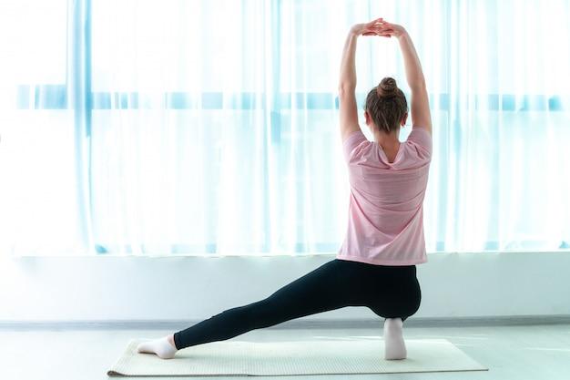 젊은 여자는 집에서 요가 매트에 근육 훈련과 피트니스 운동을합니다. 체중을 줄이고 건강을 유지하십시오. 건강한 스포츠 라이프 스타일