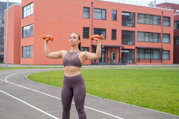 若い女性は、屋外のスタジアムでスポーツ用品を使ってスポーツトレーニングを行っています。ボディービルと健康のためのライフスタイルとトレーニングエクササイズ。