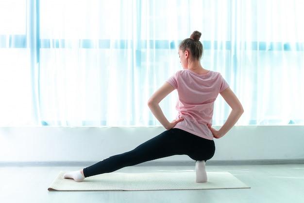 젊은 여자는 집에서 요가 매트에 근육과 피트니스 운동을 스트레칭합니다. 체중을 줄이고 건강을 유지하십시오. 건강한 스포츠 라이프 스타일