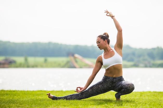 若い女性は日光と朝の公園でヨガのポーズをします