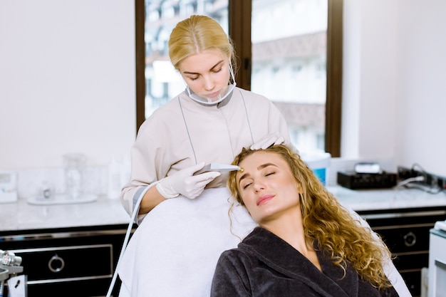 Young woman doctor cosmetologist makes the procedure of microdermabrasion of the facial skin of a beautiful
