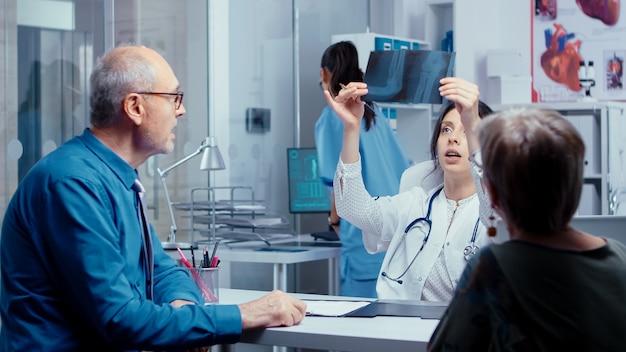 젊은 여성 의사는 그들의 문제에 대해 노부부와 이야기하면서 간호사로부터 엑스레이를 받고 있습니다. 질병 예방 및 건강 관리 문제에 대한 현대 병원 또는 개인 클리닉 건강 검진. 가볍게 두드리기