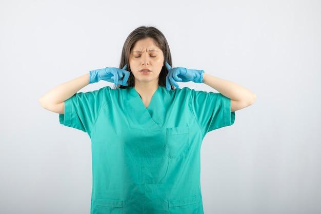 Medico della giovane donna in orecchie coning uniformi verdi con le dita indice.