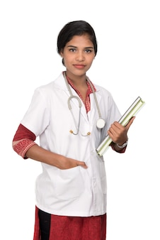 Young woman doctor holding book with stethoscope