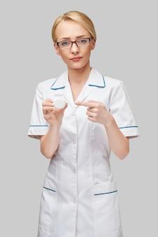Молодая женщина-врач, держащая зубную нить, чистящую резьбовую коробку для чистки зубов - стоматологическая помощь и гигиена.