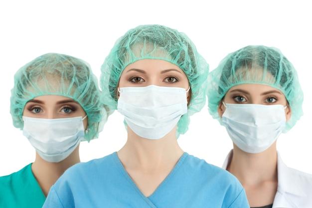 キャップとフェイスマスクの若い女性医師。2人の同僚が彼女の後ろに立っています。ヘルスケア、医療、手術、チームワークのコンセプト
