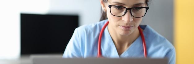 Молодая женщина-врач в очках, сидя за ноутбуком в офисе клиники