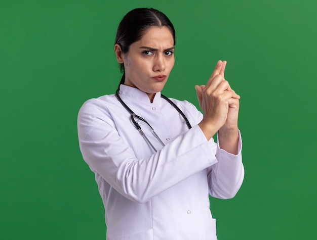 緑の壁の上に立っている指でピストルジェスチャーを作る深刻な顔で正面を見て聴診器で医療コートの若い女性医師