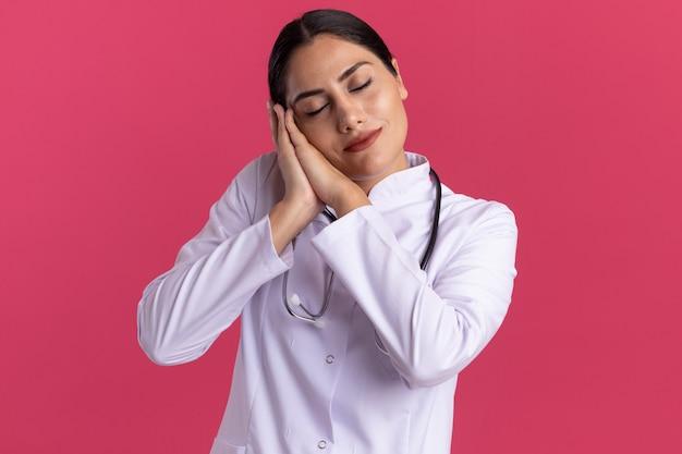 ピンクの壁の上に立っている手のひらに頭を傾けて手のひらを一緒に保持している聴診器で睡眠ジェスチャーを作る医療コートの若い女性医師