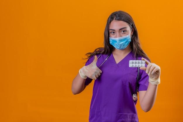 保護マスクと分離のオレンジ色の背景の上に親指を現して薬と一緒に水ぶくれを持って笑みを浮かべて手袋を着てphonendoscopeと医療の制服を着た若い女性医師